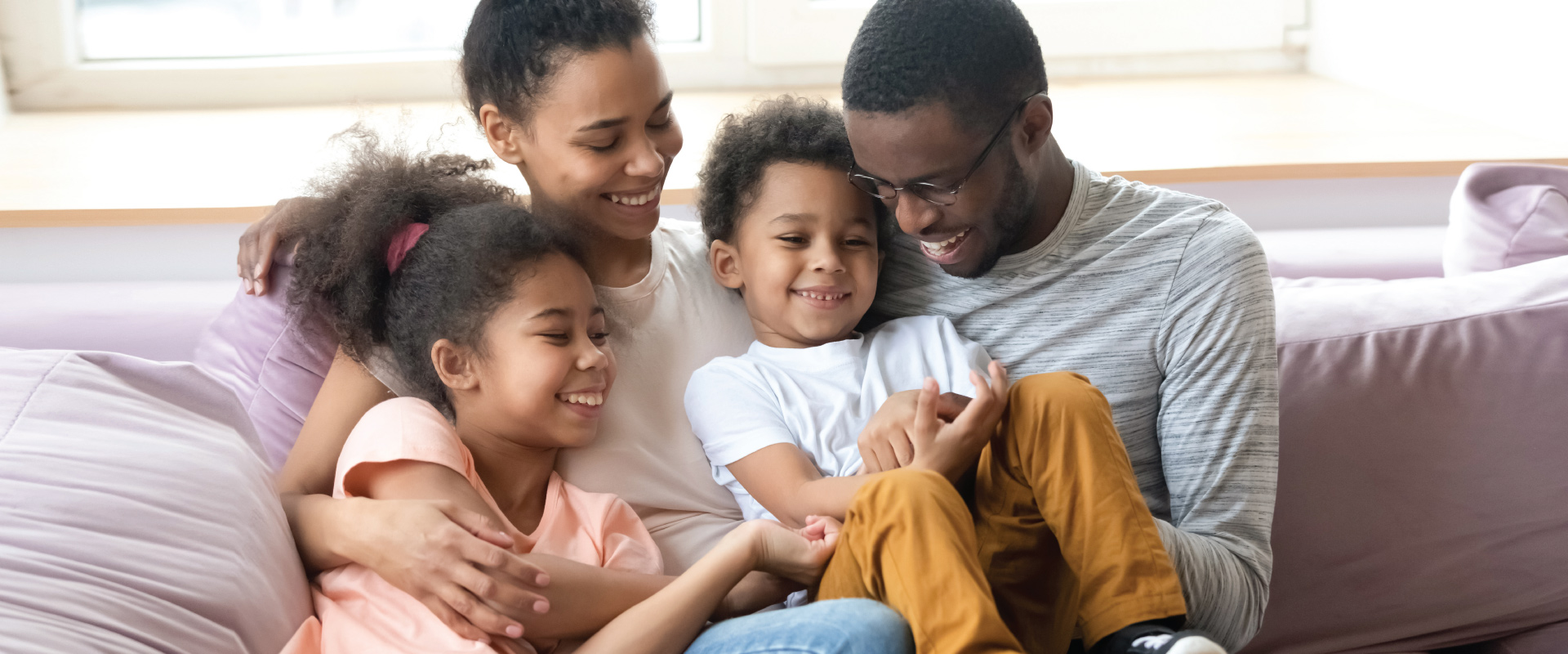 African American family sitting together on couch all smiling